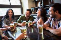 Lyckliga vänner som dricker öl på stången eller baren Royaltyfri Bild
