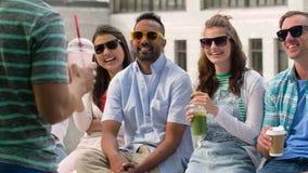 Lyckliga vänner som dricker kaffe och skakor i stad arkivfilmer