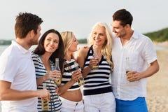 Lyckliga vänner som dricker non alkoholiserat öl på stranden royaltyfri bild