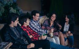 Lyckliga vänner som dricker och har gyckel i ett parti Arkivfoto