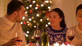 Lyckliga vänner som dricker rött vin på jul arkivfilmer