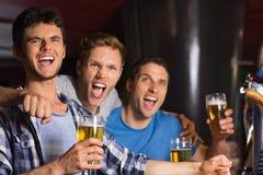 Lyckliga vänner som fångar upp över halva liter Fotografering för Bildbyråer