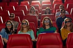 Lyckliga vänner som håller ögonen på film i teatern 3d Royaltyfria Bilder