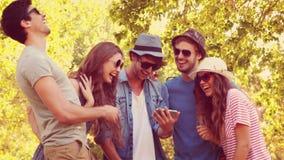 Lyckliga vänner som håller ögonen på foto på en smartphone i parkera lager videofilmer