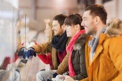 Lyckliga vänner som håller ögonen på hockeyleken på att åka skridskor isbanan Royaltyfria Foton