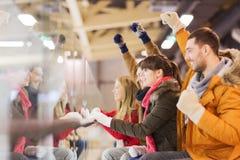 Lyckliga vänner som håller ögonen på hockeyleken på att åka skridskor isbanan Royaltyfri Bild