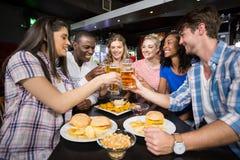 Lyckliga vänner som har en drink och en hamburgare Fotografering för Bildbyråer