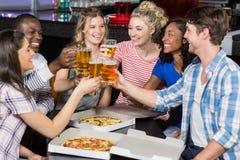 Lyckliga vänner som har en drink och en pizza royaltyfri foto