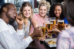 Lyckliga vänner som har en drink och en pizza royaltyfri bild