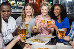 Lyckliga vänner som har en drink och en pizza Arkivfoto