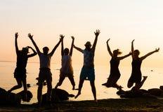 Lyckliga vänner som har ett parti på en strand Royaltyfri Bild