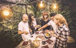 Lyckliga vänner som har gyckel som äter lokal mat på trädgårdpicknickpartiet arkivbild