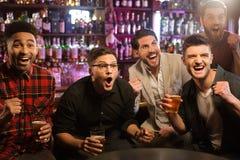 Lyckliga vänner som har gyckel i bar arkivfoto