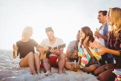 Lyckliga vänner som har gyckel, medan sitta på sand royaltyfria foton