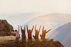 Lyckliga vänner som har gyckel på bergöverkanten royaltyfria bilder
