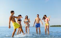 Lyckliga vänner som har gyckel på sommarstranden Royaltyfri Fotografi