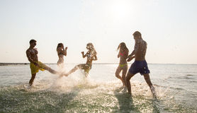 Lyckliga vänner som har gyckel på sommarstranden Arkivbilder