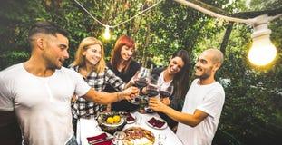 Lyckliga vänner som har gyckel som tillsammans dricker rött vin på trädgårdträdgårdpartiet - ungdomkamratskapbegrepp på lantgårdh royaltyfri foto