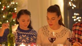 Lyckliga vänner som har julmatställen hemma arkivfilmer