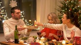 Lyckliga vänner som har julmatställen hemma lager videofilmer