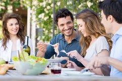 Lyckliga vänner som har lunch Fotografering för Bildbyråer