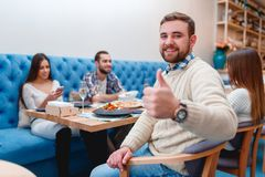Lyckliga vänner som har matställen i bra restaurang royaltyfria bilder
