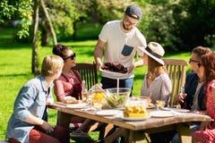 Lyckliga vänner som har matställen på det trädgårds- partiet för sommar Royaltyfri Bild