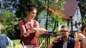 Lyckliga vänner som har matställen på det trädgårds- partiet för sommar stock video