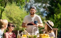 Lyckliga vänner som har matställen på det trädgårds- partiet för sommar arkivbild