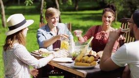 Lyckliga vänner som har matställen på det trädgårds- partiet för sommar arkivfilmer