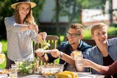 Lyckliga vänner som har matställen på det trädgårds- partiet för sommar Arkivbilder