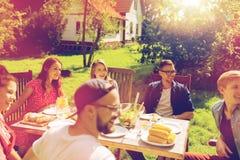 Lyckliga vänner som har matställen på det trädgårds- partiet för sommar royaltyfria foton