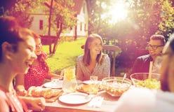 Lyckliga vänner som har matställen på det trädgårds- partiet för sommar royaltyfri fotografi