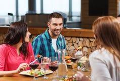 Lyckliga vänner som har matställen på restaurangen arkivfoton