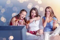 Lyckliga vänner som hemma äter pizza och håller ögonen på tv royaltyfria bilder