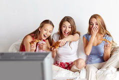 Lyckliga vänner som hemma äter pizza och håller ögonen på tv arkivfoto