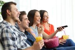 Lyckliga vänner som hemma håller ögonen på tv Arkivbilder