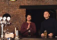 Lyckliga vänner som hurrar för favorit- lag i bar fotografering för bildbyråer