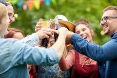 Lyckliga vänner som klirrar exponeringsglas på sommarträdgården Royaltyfria Foton