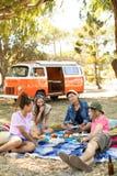 Lyckliga vänner som kopplar av på fält under picknick royaltyfria bilder
