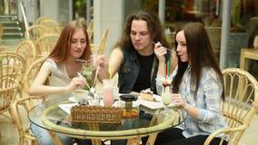 Lyckliga vänner som möter och dricker te eller kaffe på kafét arkivfilmer