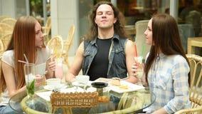Lyckliga vänner som möter och dricker te eller kaffe på kafét lager videofilmer