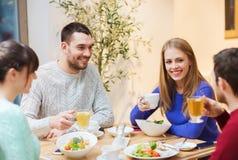 Lyckliga vänner som möter och har matställen på kafét Arkivfoto