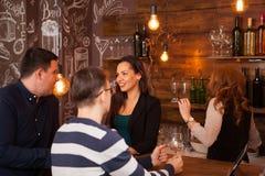 Lyckliga vänner som påverkar varandra på stångräknaren i en bar fotografering för bildbyråer