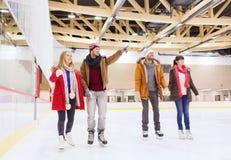 Lyckliga vänner som pekar fingret på att åka skridskor isbanan Arkivbild