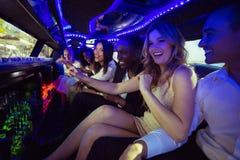 Lyckliga vänner som pratar i limousine Royaltyfri Foto