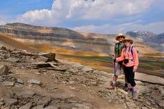 Lyckliga vänner som reser i kanadensiska steniga berg Arkivfoton
