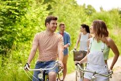 Lyckliga vänner som rider det fixade kugghjulet, cyklar i sommar arkivfoto