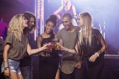 Lyckliga vänner som rostar ölexponeringsglas med aktören som sjunger i bakgrund Royaltyfri Foto