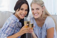 Lyckliga vänner som rostar med champagne och ser kameran Royaltyfri Foto